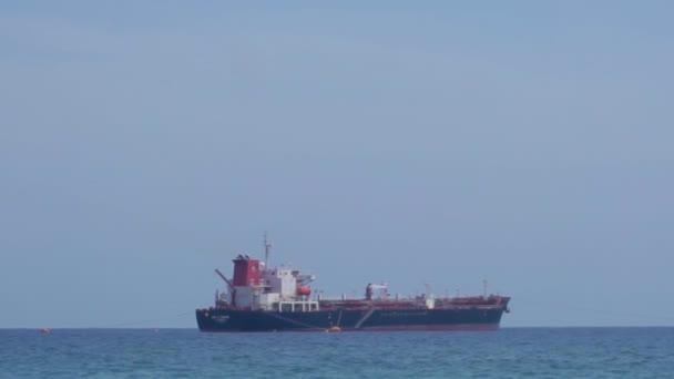 V moři na slunci se tyčí osamělá nákladní loď