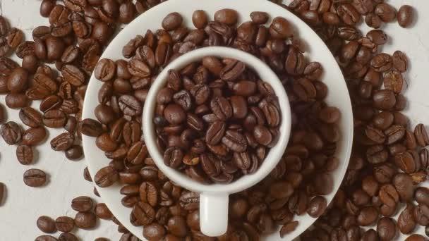 pohled shora káva pohár naplněný kávovou fazolemi. kávové boby jsou v krásně texturované tabulce
