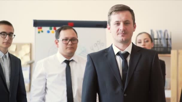 Office workers stand in line behind boss and clap their hands, boss stands with his arms folded on his chest