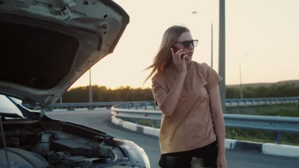 A frustrated attractive business woman on the side of the road tries to get help with her broken down car by making a phone call