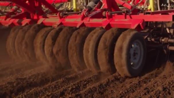 A vörös vetőmag betakarító veti a búzamagot a mezőn. A vetőmagvető gép a mezőn működik. A vetőgép elhalad a kezelő mellett