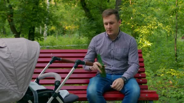Můj otec pije pivo ze zelené láhve sedící na lavičce v parku vedle kočárku. Bezstarostný otec pije alkohol s novorozeným dítětem v parku