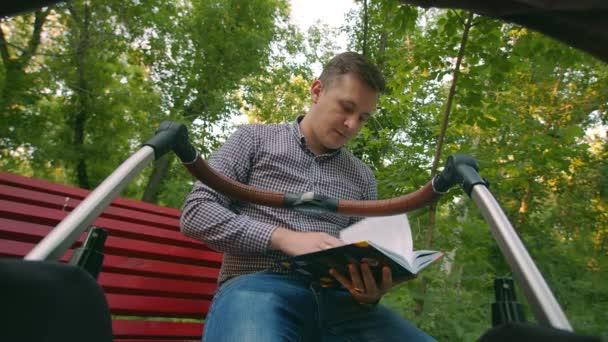 Otec na procházce s dítětem v kočárku sedí na lavičce, čte si knihu, pak válí kočárek a dívá se na dítě, pohled z kočárku. Otec houpe kočárkem a čte si knihu