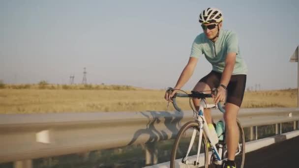 Sebevědomý cyklista na silničním kole na dálnici, s helmou a speciálními brýlemi. Muž v těsných kraťasech, helmě a brýlích, jede podél dálnice na speciálním kole s