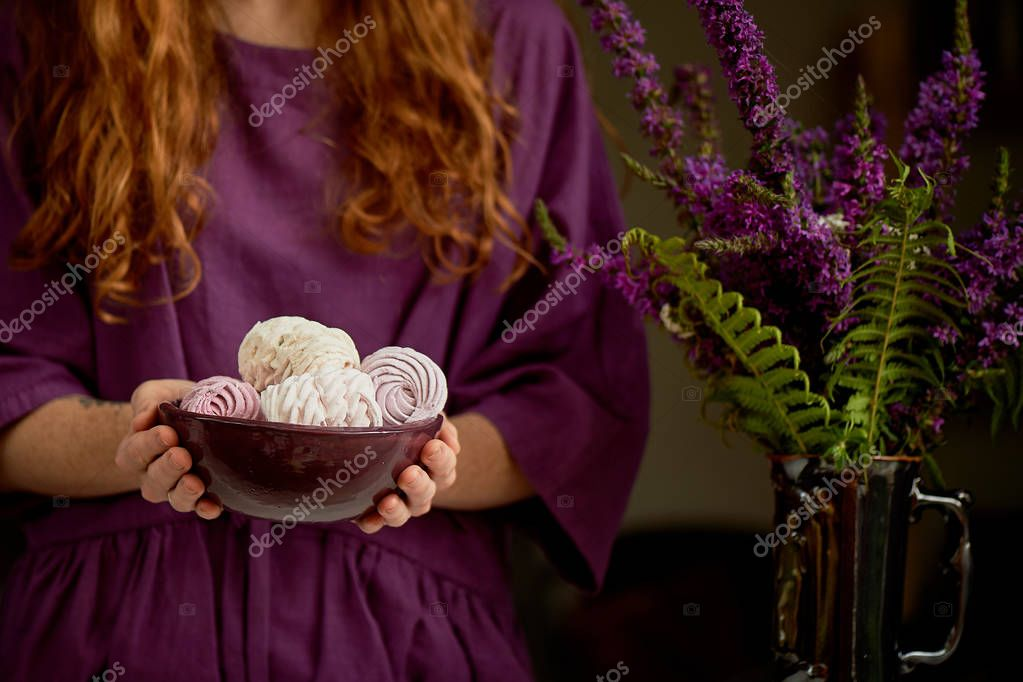 Redhaired girl in a purple dress holding a massive clay bowl with marshmallows.