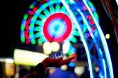 Ruské kolo skrz skleněnou kouli na dlani vaší ruky. Atmosféru oslav a odpočinku. Večerní dobrodružství. Světlé barvy. Ruky silueta