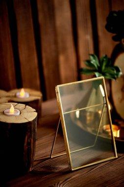 Altın çerçeve, küçük kütükler içinde led mumlar. Rahat dekor.
