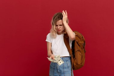 Portrait of a girl with curly blond hair, orange backpack and white headset dressed in a white t-shirt standing on a red background expressing puzzled emotion because she doesn't have enough money.
