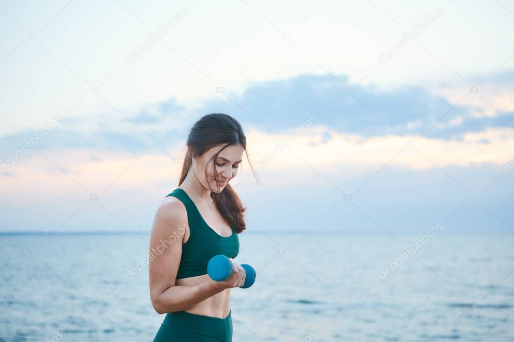 Young brunette woman exercising with dumbbells at the sea shore at sunrise.