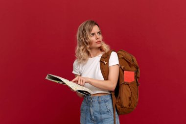 Confused blond girl with curly hair in a white t-shirt trying to find itinerary with the map holding brown orange backpack