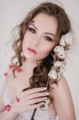 Fotografie Cosmetics and manicure. Close-up portrait of attractive woman with dry flowers on her face, pastel color, perfect make-up and skin. Fresh, trendy, spring retouched portrait