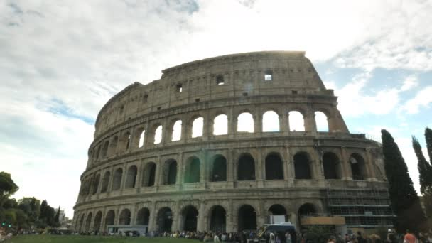 a view of the colosseum backlit by the midday sun in rome, italy