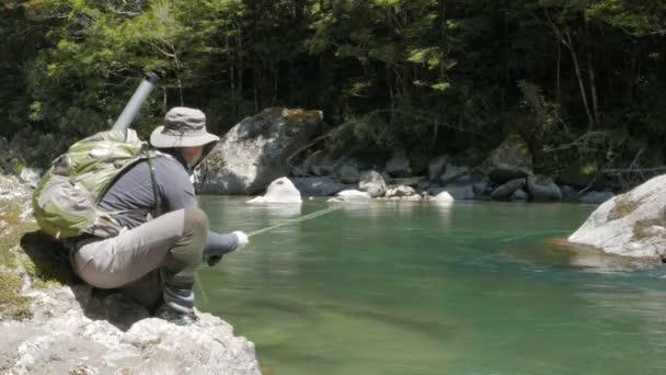 alacsony szög lövés a légy halász, bottal akasztás a pisztráng, a folyó maruia, Új-Zéland