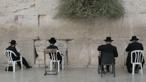 négy ülő ember, imádkozva a siránkozás fal Jeruzsálemben