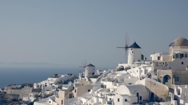 odpolední záběr nabílených domů a větrných mlýnů na Oia, Santoríni