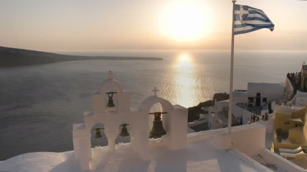 greek flag and four bells at sunset in oia, santorini