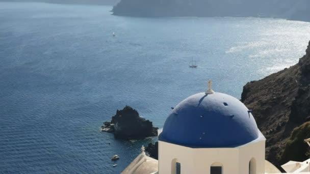 modrý klenovaný kostel s jachtou v pozadí Oia, Santoríni