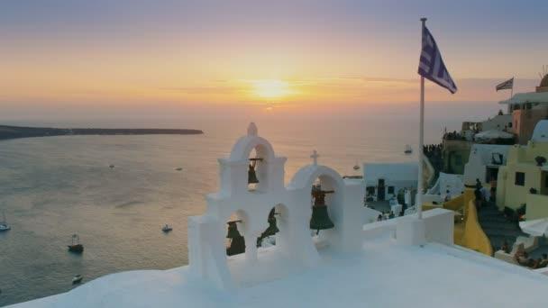 Západ slunce s řeckou vlajkou a kostelní zvony na Oia, Santoríni