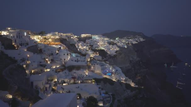 night shot of the main town of fira on santorini