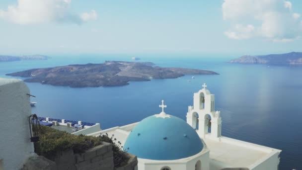 široký pohled na tři zvonky, modrou kupoli a sopku na Firu, Santoríni