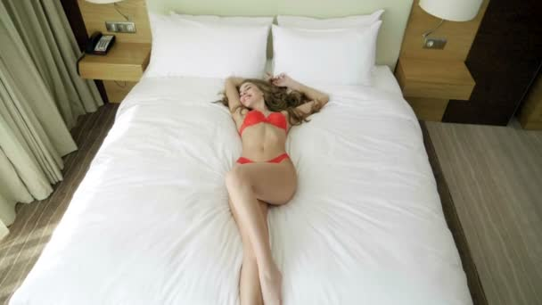 Attractive blonde woman in red lingerie lying in a white bed. Slow motion. HD