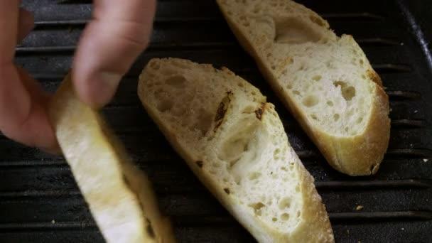 Detailní záběr tři plátky bagety právě smažit na pánev pro Italská bruschetta. 4k