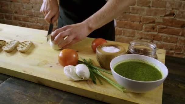 Chef cooking italian food. Bruschetta with tomatoes, mozzarella cheese, sauce pesto, green onion. 4K