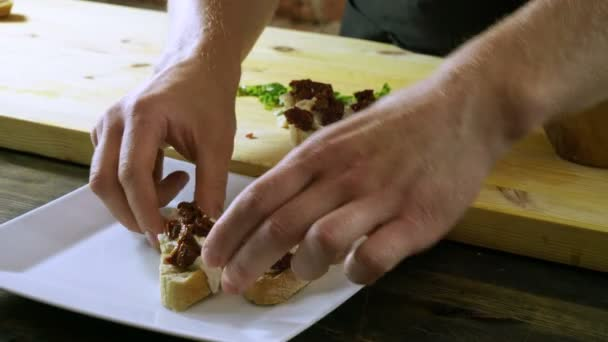 Chef cooking italian food. Bruschetta with dried tomatoes, mozzarella cheese, balsamico sauce, green onion. 4K