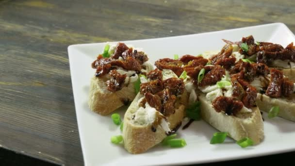 Italian food. Bruschetta with dried tomatoes, mozzarella cheese, balsamico sauce, green onion. 4K
