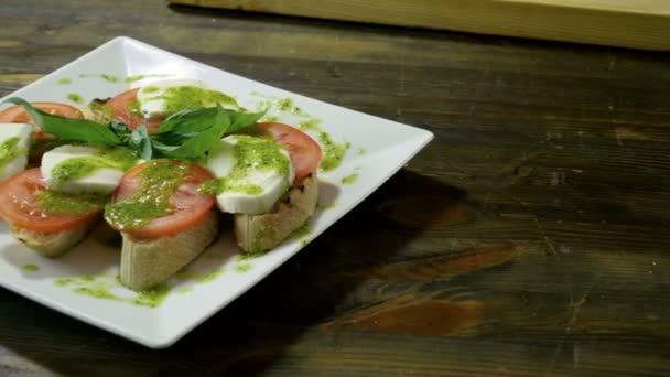 Italian food. Bruschetta with tomatoes, mozzarella cheese, pesto sauce, green onion, fresh basil. 4K
