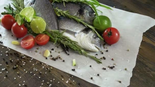 Zutaten zum Kochen von Fisch. frischer Wolfsbarsch, grüne Zwiebeln, Limetten, Knoblauchzehen, Rosmarin, Gewürze. 4k