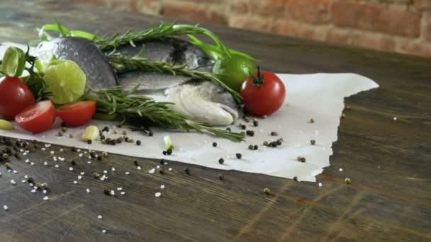 Összetevők a főzés hal. Friss tengeri sügér, zöld hagyma, lime, gerezd fokhagyma, rozmaring, ízesítésére. 4k