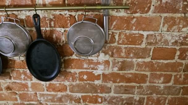 Interiér kuchyně. Panorama litinové pánve, síta, metla, dřevěné krájecí desky na cihlovou zeď na pozadí. 4k