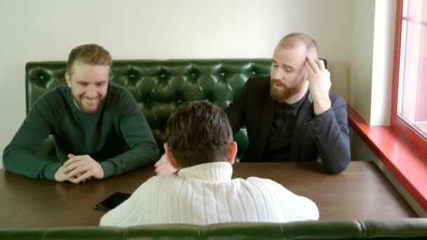 Meeting of friends. Three handsome men talking and laughing in a restaurant. 4K