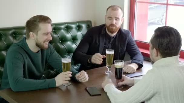 Egy cég, a jóképű három férfi meg beszél, és a sört. 4k