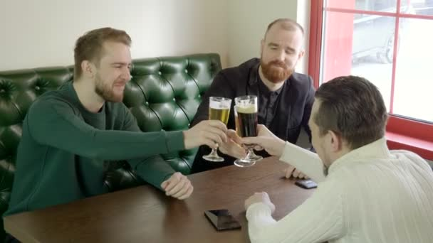 The young smiling men clinking glasses of beer in a pub. 4K
