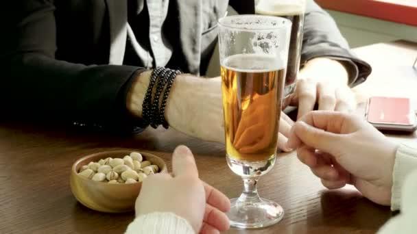 Close-up shot mužských rukou s dvě sklenice piva v restauraci. 4k