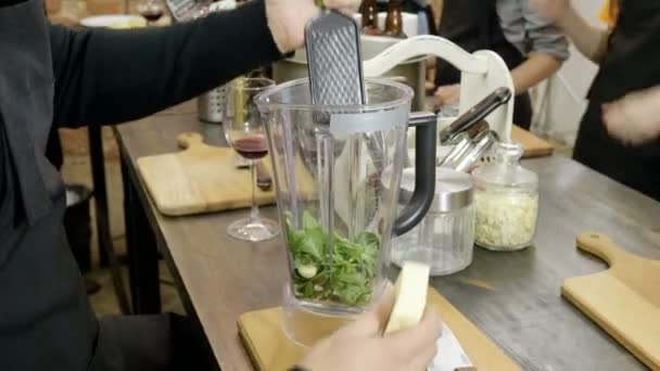 The man rubbing parmesan cheese on the metal grater for pesto sauce at cooking master class. 4K
