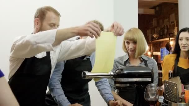 Koch zeigt Schülern, wie man eine Teigrolle bedient. 4k
