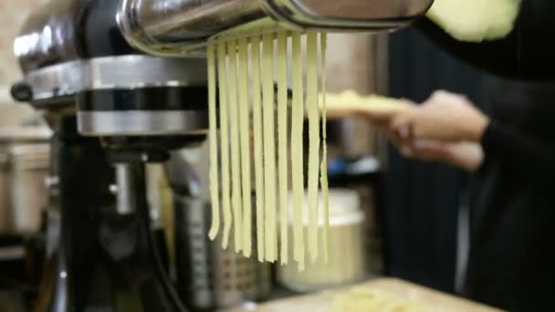 Group of people making pasta from dough using pasta machine at cooking master class. 4K