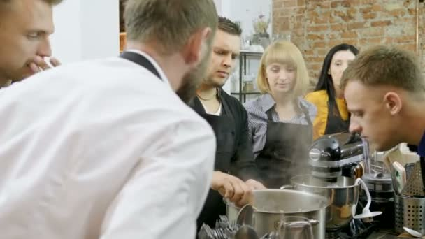 Young men and woman preparing mussels with wine, chopped onions, garlic,  vegetable oil, cream at the cooking master class  4K