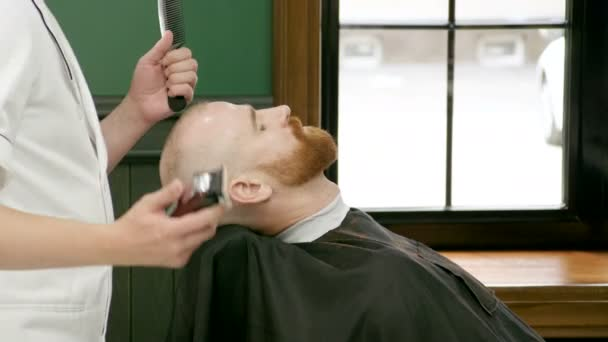 Mens hairstyling and haircutting in a barbers or hair salon. Barber cutting mens face hair at barbershop. 4K