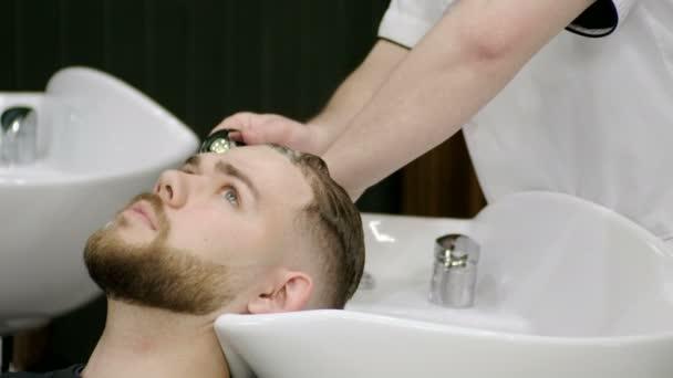 Příprava na účes. Mužské holič mytí hlavu mladého muže v holiči. 4k