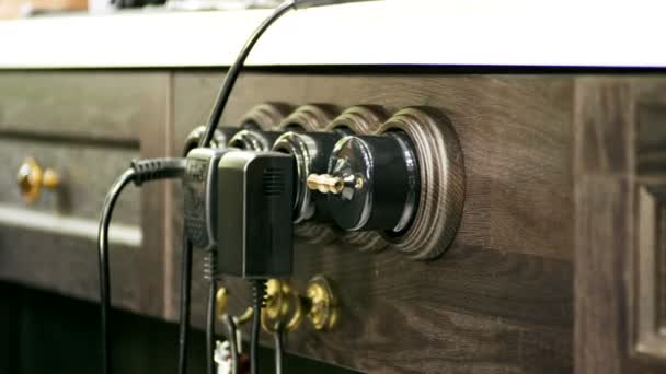 Tři elektrické zástrčky do zásuvky. Detailní záběr elektrických zásuvek, kabel na dřevěnou truhlu. 4k