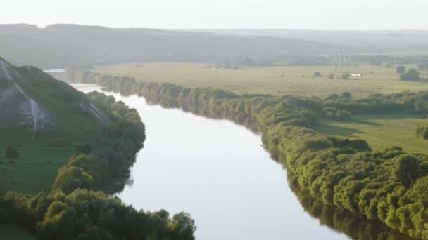 Jarní krajina. Pohled shora řeky uprostřed zelený les a louku. 4k