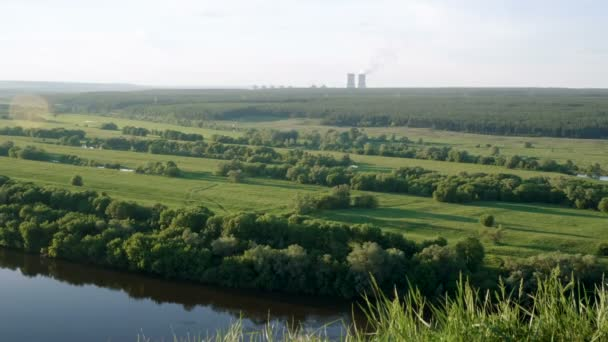 Flusslandschaft, Wald, Wiese mit einem Atomkraftwerk im Hintergrund 4k