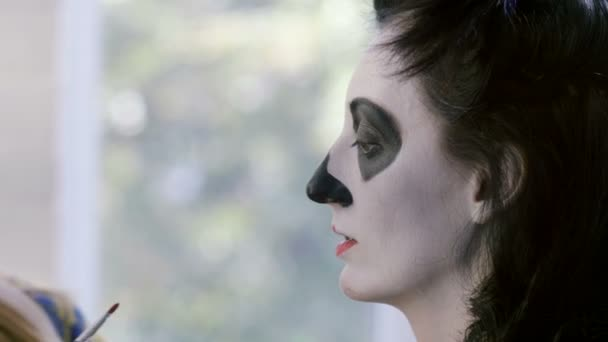 Halloween party. Make-up artist is making woman up as skeleton for celebration of the Mexican Day of the Dead. 4K