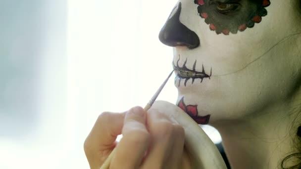 Halloween-Party. Make-up-Artist macht Frau als Schädel für Feierlichkeiten zum mexikanischen Tag der Toten. 4k