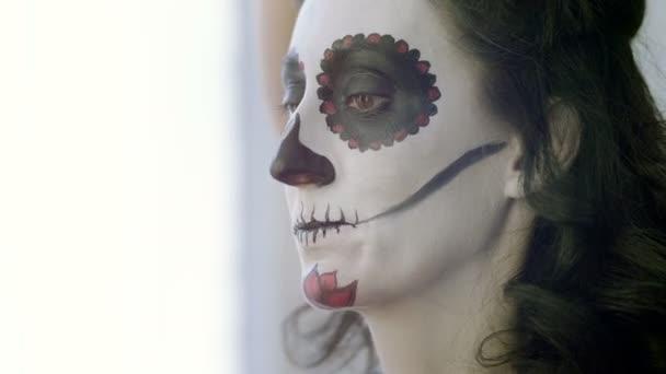 Halloween-Gesichtskunst. Visagistin schminkt Frau als Skelett zur Feier des mexikanischen Tages der Toten. 4k