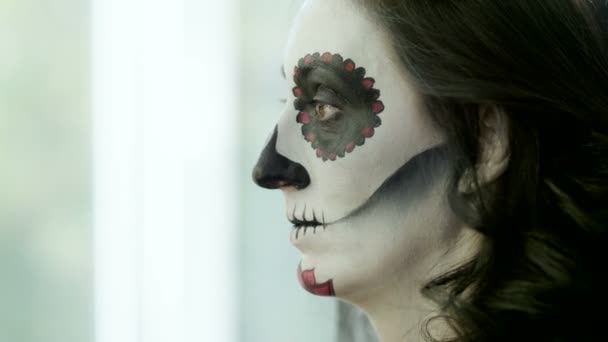 Halloween face art. Make-up artist is making woman up as skeleton for celebration of the Mexican Day of the Dead. 4K